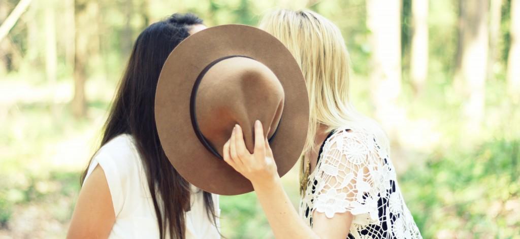 twee vrouwen zoenen achter hoed